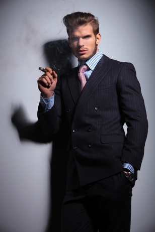 young man with hand in pocket  is smoking a cigar